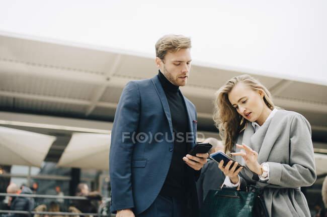 Vista de bajo ángulo de las empresarias que utilizan el teléfono mientras se encuentran junto a colegas en la ciudad. - foto de stock