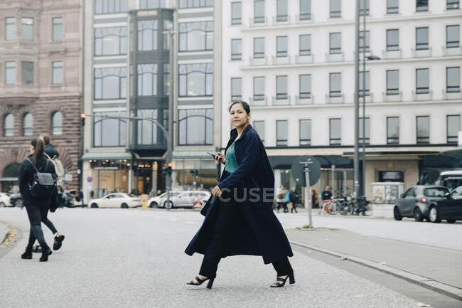 Portrait of female entrepreneur wearing jacket crossing road in city — Stock Photo