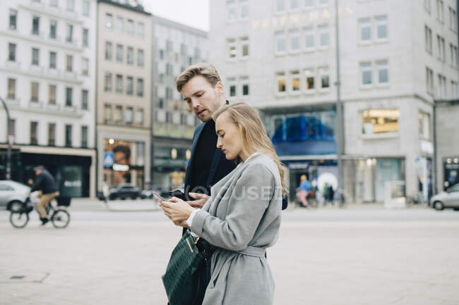 Side view of businesswoman using phone while walking by colleague in city — Stock Photo