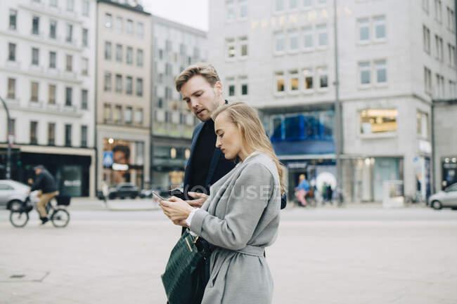 Vista lateral de las empresarias que utilizan el teléfono mientras caminan por la ciudad. - foto de stock