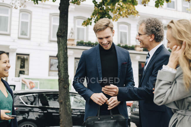 Smiling entrepreneur showing mobile phone to male colleague while standing by colleagues in city — Stock Photo