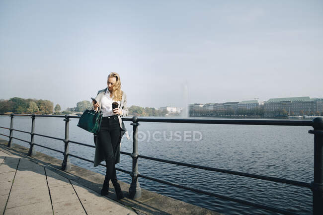 Full length of entrepreneur using mobile phone while standing against sea in city — Stock Photo