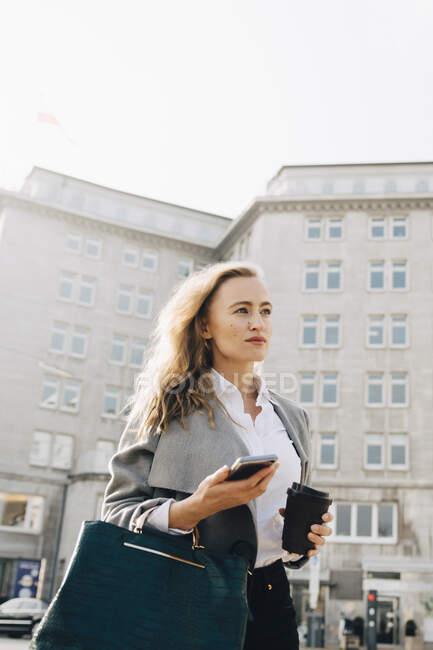 Vista de bajo ángulo de la contemplación del empresario con el teléfono móvil mirando hacia otro lado mientras está de pie en la ciudad. - foto de stock