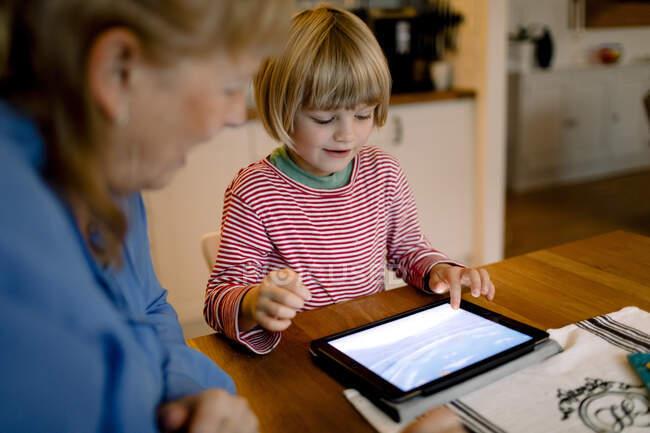 Grand-mère regardant petit-fils en utilisant une tablette numérique — Photo de stock