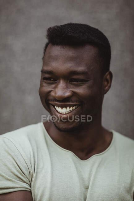 Закрытие счастливого человека, отводящего взгляд, стоя на улице — стоковое фото
