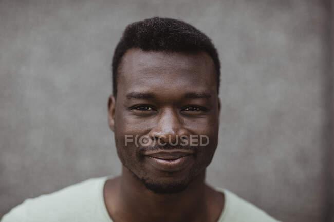 Закрытый портрет улыбающегося человека, стоящего на улице — стоковое фото