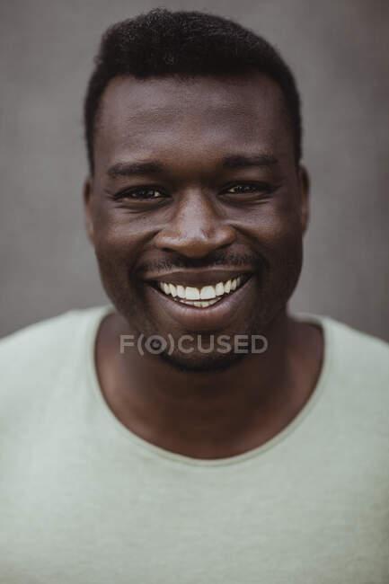 Закрытый портрет счастливого человека, стоящего на улице — стоковое фото