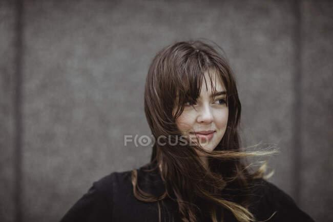 Усміхнена жінка відвернулася, стоячи надворі. — стокове фото