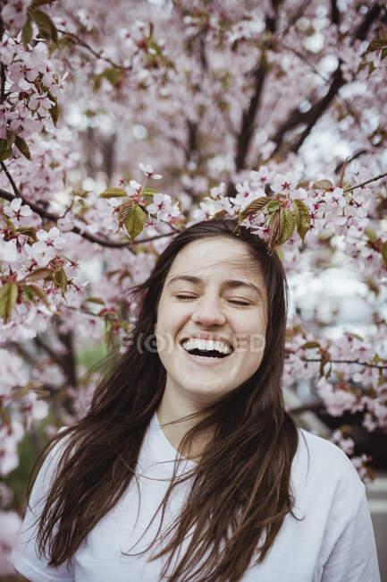 Lächelnde junge Frau steht gegen rosa Baum — Stockfoto