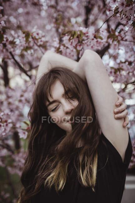 Посміхнена жінка з закритими очима на дерево. — стокове фото
