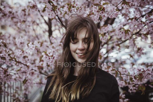 Усмішка молода жінка стоїть навпроти дерева. — стокове фото