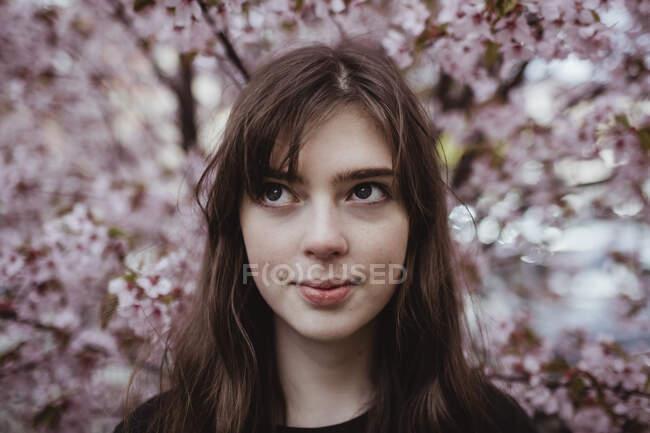 Усміхнена молода жінка відвернулася, стоячи навпроти дерева. — стокове фото