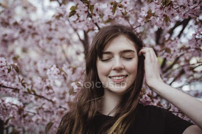 Посмішка жінка з заплющеними очима стоїть проти дерева. — стокове фото