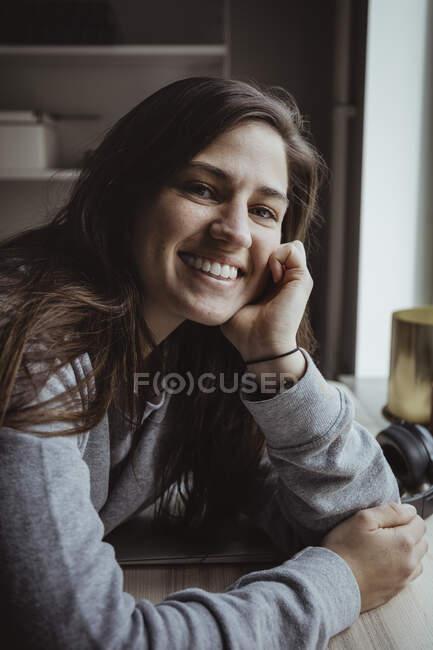 Портрет усміхненої жінки за столом. — стокове фото