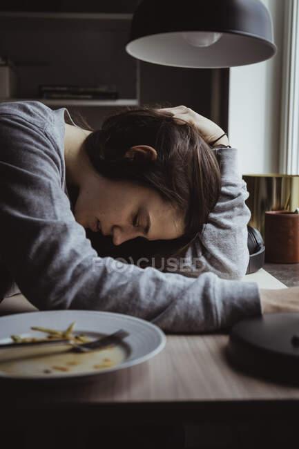 Seitenansicht einer traurigen Frau am Tisch — Stockfoto