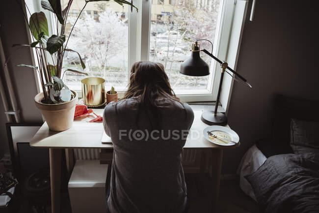 Передній вид стурбованої жінки сидить навпроти вікна. — стокове фото