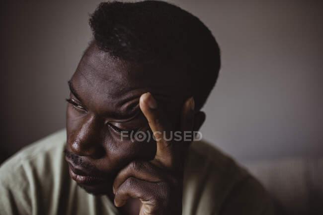 Nahaufnahme eines traurigen Mannes, der den Kopf in der Hand hält und wegschaut — Stockfoto