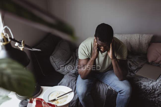 Високий кут зору людини з головою в руках сидячи на ліжку вдома. — стокове фото