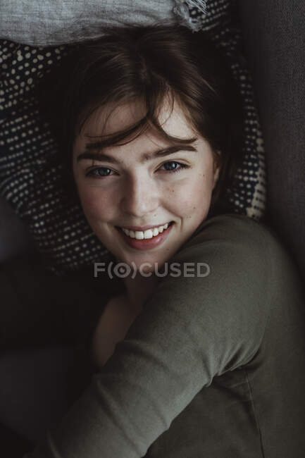 Portrait of smiling woman on sofa — Stock Photo