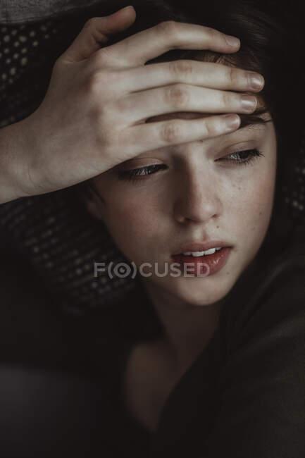 Nahaufnahme einer Frau mit Kopfschmerzen beim Wegschauen auf dem Sofa — Stockfoto