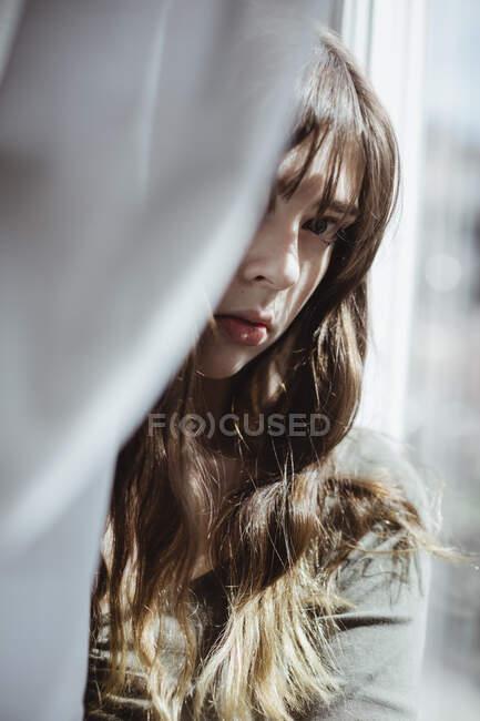 Портрет жінки, що ховається за вікном. — стокове фото