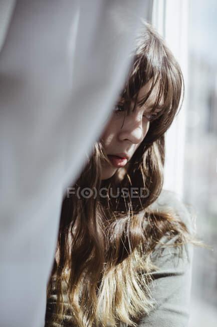Закриття молодої жінки, що ховається за вікном завіси. — стокове фото