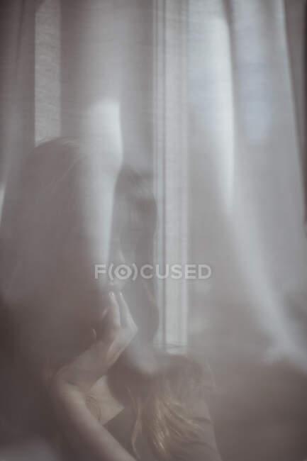 Frau versteckt sich hinter weißem Fenstervorhang — Stockfoto