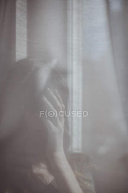Молода жінка ховається за білою віконною завісою. — стокове фото