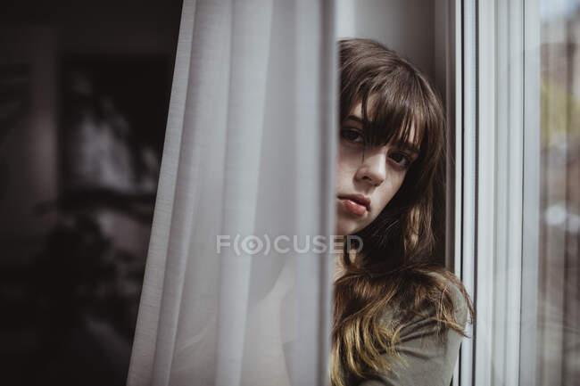 Портрет жінки за завісою вікна. — стокове фото