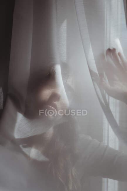 Frau versteckt sich hinter weißem Vorhang — Stockfoto