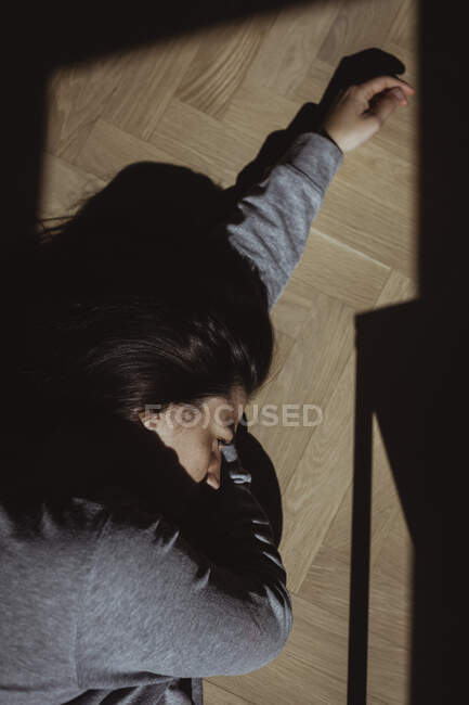 Close-up of stressed woman lying on floor at home — Stock Photo