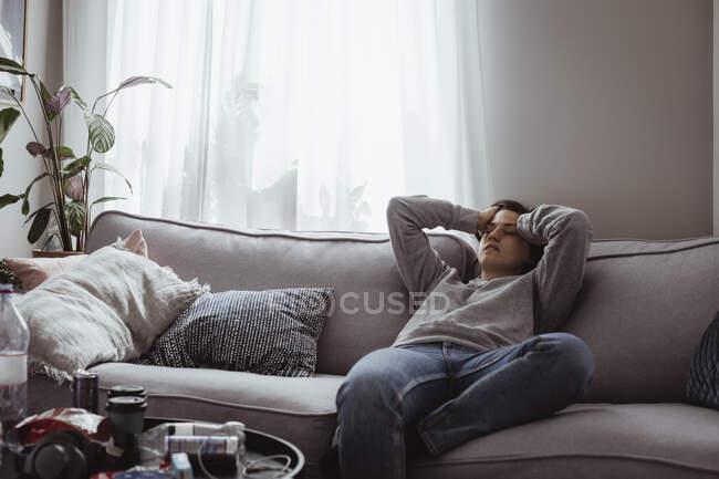 Молода жінка з головним болем сидить вдома на дивані. — стокове фото