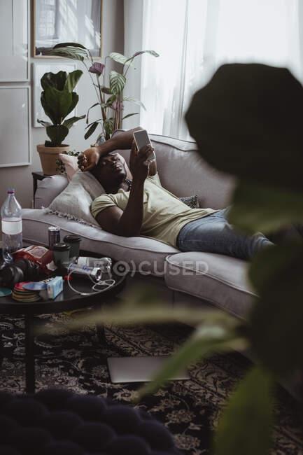 Sad man using smart phone while lying on sofa at home — Stock Photo