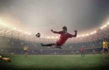 Football player kicking in front of floodlights — Stock Photo