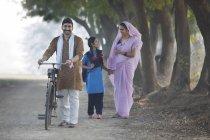 Felice coppia rurale con figlia a piedi sulla strada del villaggio — Foto stock