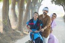 Felice coppia rurale insieme a figlia in bicicletta al villaggio — Foto stock
