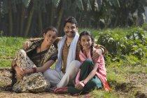Lächelnde indische Familie sitzt auf dem Feld — Stockfoto