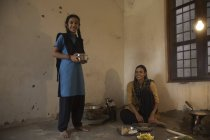 Indian rural woman sitting in kitchen on floor while daughter standing with tiffin box — Stock Photo