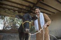 Усміхаючись індійських фермерів чоловічого поблизу чорний корови в сарай — стокове фото