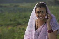 Porträt einer lächelnden Landfrau, die den Kopf mit einem Sari bedeckt, der am Telefon spricht — Stockfoto