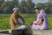 Coppia indiana seduta vicino al serbatoio d'acqua in campo agricolo — Foto stock