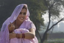 Крупним планом усміхнений сільська жінка сидить біля сільському господарстві, сфері покриття голову з Сарі — стокове фото