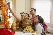 Індійська сім'ї в святковий одяг святкування Ганеш chaturthi в приміщенні — стокове фото