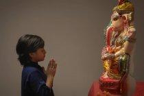 Se juntou a mulher rezando com mãos e olhos fechados em frente do ídolo Ganpati — Fotografia de Stock