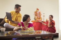 Indian young adult couple looking on old woman near religious Idol — Stock Photo