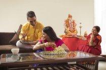 Indian family in festive clothes celebrating ganesh chaturthi indoors — Stock Photo
