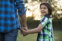 Задній вид щасливі хлопчика, що тримається боку батька в парку — стокове фото