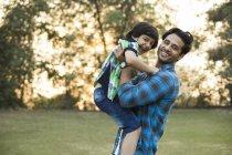 Улыбающийся индеец, играющий с ребенком в парке — стоковое фото