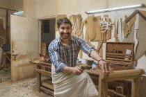 Lächelnder Schreiner arbeitet in Werkstatt mit Hammer — Stockfoto