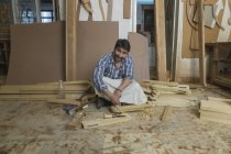 Carpenter working with chisel and hammer on floor in workshop — Stock Photo